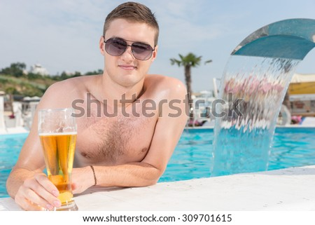 Close up Handsome Young Man with Sunglasses, Holding a Glass of Beer While Leaning on the Edge of the Swimming Pool and Smiling at the Camera. - stock photo