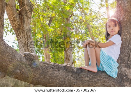 Close up happy adorable asian children climbing trees with sun flare. - stock photo