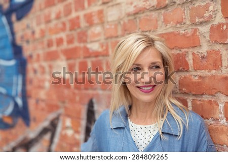 Close up Happy Adult Woman with Blond Hair Leaning Against Old Brick Wall While Looking Into Distance. - stock photo