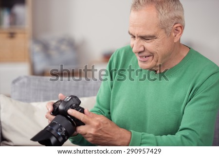 Close up Happy Blond Middle Aged Man Viewing his Captured Pictures on DSLR Camera While Sitting on the Couch. - stock photo