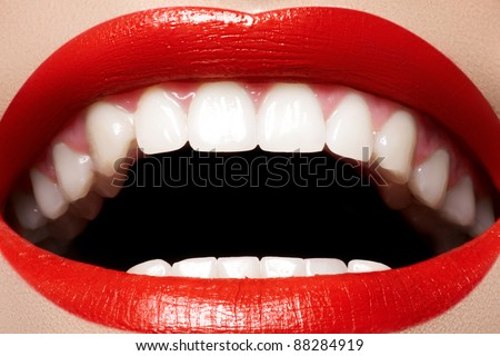 Close-up happy female smile with healthy white teeth, bright red gloss lips make-up. Cosmetology, dentistry and beauty care. Macro of woman's smiling mouth
