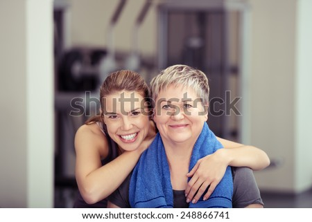 Close up Happy Fit Daughter Leaning to Healthy Mom While at the Fitness Gym, Looking at the Camera. - stock photo