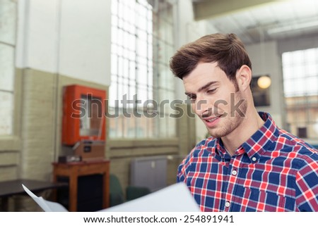 Close up Happy Good Looking Young Man Looking at the Report Paper Inside the Office. - stock photo