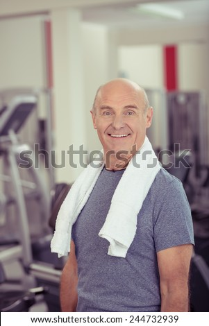 Close up Happy Healthy Old Bald Man, with Towel at his Shoulder, at the Fitness Gym.