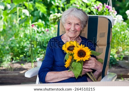 Close up Happy Old Lady in Blue Dress  Sitting on a Chair at the Garden, Holding Fresh Sunflowers While Looking at the Camera. - stock photo