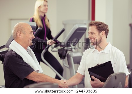 Close up Happy Old Man Shaking Hands with his Young Male Instructor at the Fitness Gym - stock photo