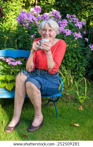 Close up Happy Old Woman Having a Cup of Coffee at the Blue Bench at the Garden. - stock photo