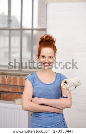Close up Happy Pretty Woman with Arms Crossed Standing Inside the While Holding a Paint Roller While Looking at the Camera. - stock photo