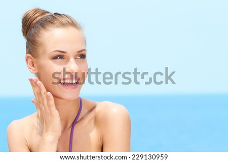 Close up Happy Slim Blond Woman Looking at her Upper Left Side with Beautiful Beach on the Background. - stock photo