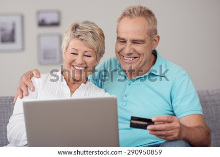 Close up Happy Sweet Senior Couple Sitting at the Couch, Using a Laptop Computer for Some Online Transaction. - stock photo