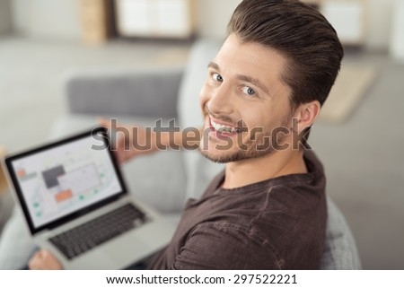 Close up Happy Young Bearded Handsome Man Looking at the Camera While Browsing Internet Using his Laptop Computer at the Couch