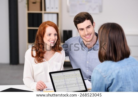 Close up Happy Young Couple Listening to a Businesswoman Talking About Plans at the Worktable Inside the Office. - stock photo