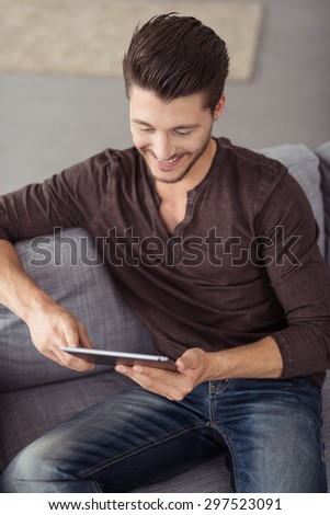Close up Happy Young Guy Using his Tablet Computer While Relaxing on the Couch at the Living Room. - stock photo