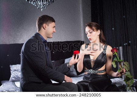 Close up Happy Young Man Offering Jewelry Gift to his Sexy Girlfriend While Both are Sitting on the Bed. - stock photo