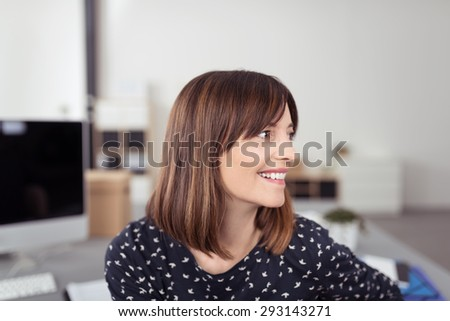 Close up Happy Young Office Woman with Brown Hair, Sitting at her Table While Looking to the Right of the Frame. - stock photo