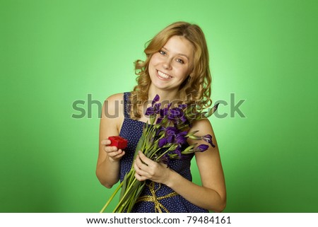 Close-up Happy young woman in one hand holding a bouquet of irises and other red gift box. Marriage proposal