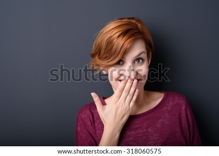 Close up Happy Young Woman Smiling at the Camera While Covering her Mouth with her Hand Against Gray Background with Copy Space. - stock photo