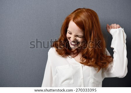 Close up Happy Young Woman with Brown Hair Raising her Arm for Success. Captured in Studio with Gray Background. - stock photo