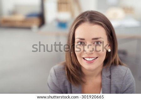 Close up Head and Shoulder Shot of a Pretty Young Office Worker Looking at the Camera with a Toothy Smile. - stock photo