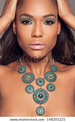 Close up head portrait of a beautiful African fashion model wearing a striking ethncs necklace posing with her hands to her hair - stock photo