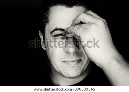 Close up head portrait of a middle aged young looking male in black and white monochrome. The man holds his nose and sinus area with fingers in obvious pain from a head ache in the front forehead area - stock photo