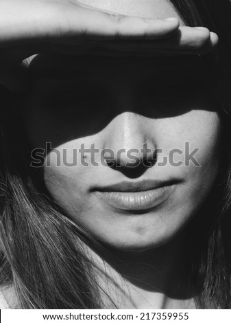 Close up head portrait of an attractive young woman shielding her eyes from the bright summer sun casting a dark mysterious shadow over her face - stock photo