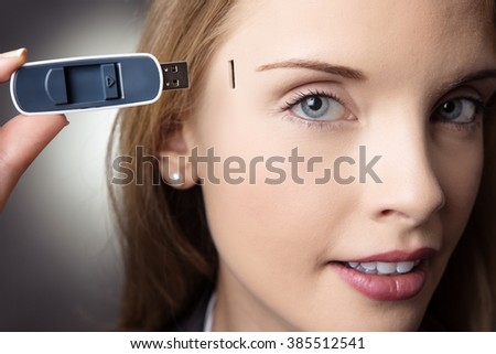 Close-up head shot of a business woman holding a memory stick to the side of her head