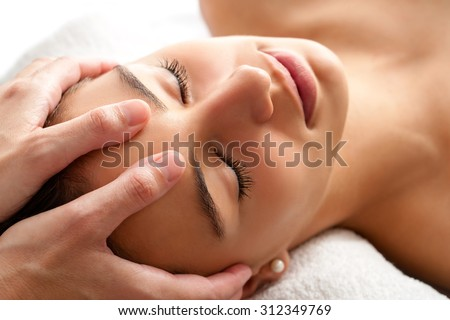 Close up head shot  of Woman having curative facial massage. Therapist applying pressure with thumbs on forehead.