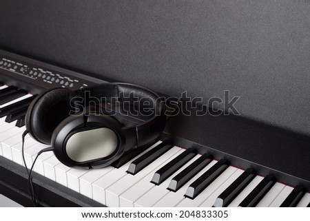 Close-up headphones on piano keyboard - stock photo