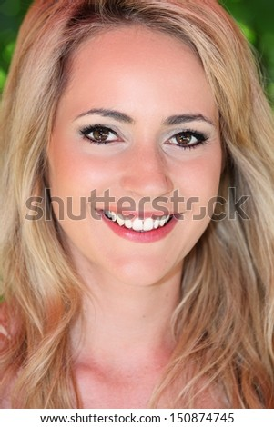 Close up headshot portrait of a beautiful blond woman with a lovely smile and subtle makeup - stock photo
