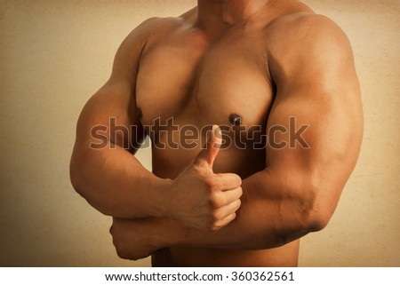 Close up healthy fit man body with thumb up gesture, grunge vintage style. - stock photo