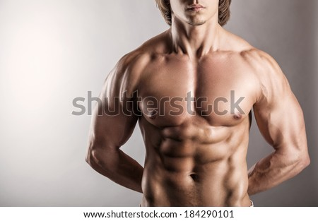 Close-up healthy muscular young man on a gray background - stock photo