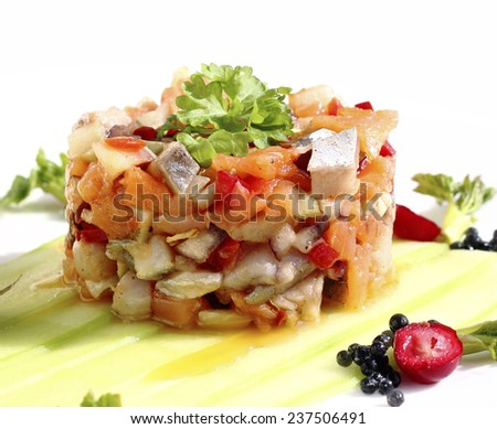 Close up herring salad with smoked salmon and vegetables - stock photo