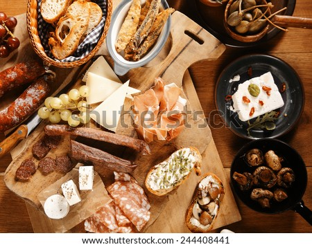 Close up High Angle Shot of Assorted Mouth Watering Tapas on Wooden Table, Emphasizing Meats, Cheese and Breads - stock photo