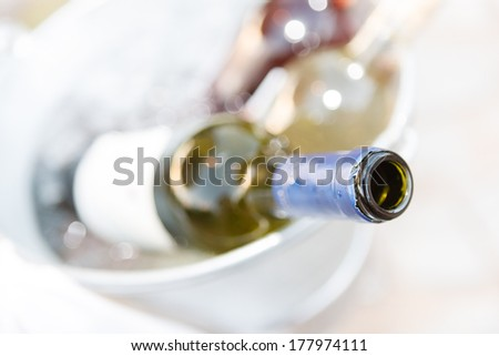 Close up high angle view of the open neck of a bottle of wine in a wine cooler for entertaining at a special event - stock photo