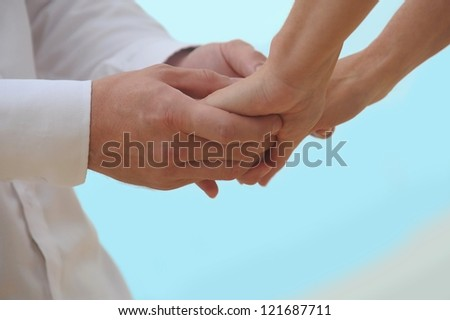 Close-up Holding Hands Married couples holding hands, a warm ocean water on a blue background. - stock photo