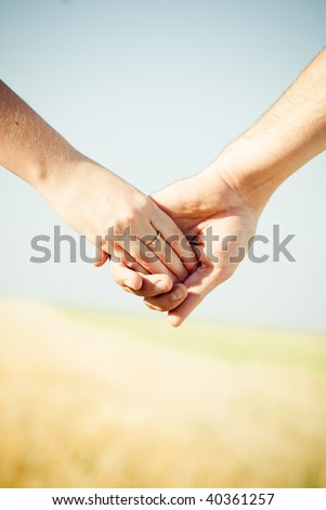 Close-up Holding Hands with Wedding Ring - stock photo