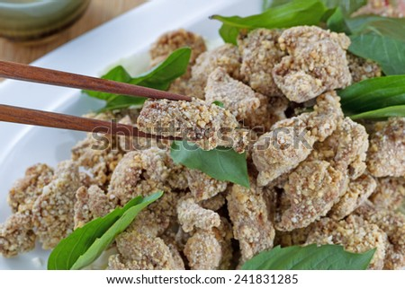 Close up horizontal image of Chinese sliced fried cooked chicken, focus on single piece being picked up with chopsticks, in white dish with ceramic cup in background on natural bamboo background  - stock photo