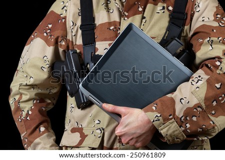 Close up horizontal image of laptop computer with armed male soldier holding it while on black background.  - stock photo