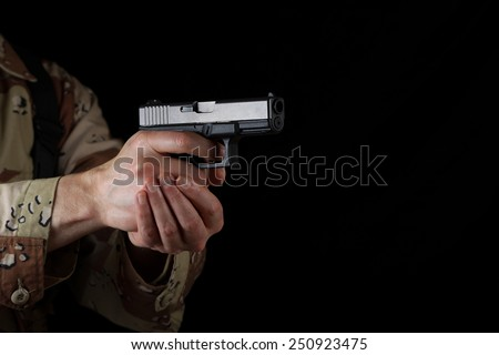Close up horizontal image of pistol, pointing sideways into darkness, with armed male soldier in background. Focus on side part of weapon. Lighting effect for night time concept.  - stock photo