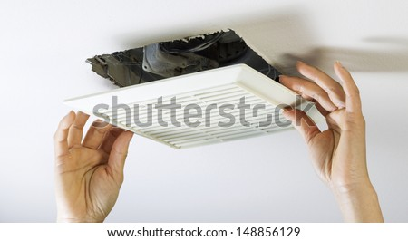 Close up horizontal photo of female hands removing bathroom fan vent cover from ceiling  - stock photo