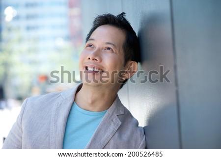 Close up horizontal portrait of a smiling asian man - stock photo