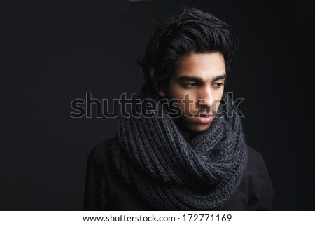 Close up horizontal portrait of an attractive young man in wool scarf posing on dark gray background