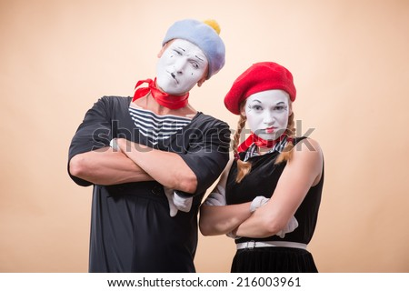Close-up horizontal portrait of couple of two funny mimes, female mime looking irritating at the camera and male mime looking at his partner isolated on beige background with copy place - stock photo