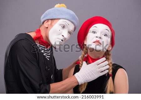 Close-up horizontal portrait of couple of two funny mimes, male mime strangulating female mime looking angry at the camera and isolated on grey background  - stock photo