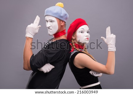 Close-up horizontal portrait of couple of two mimes standing back to back and showing a gun with their hands, female mime looking at the camera, male looking aside and isolated on grey background  - stock photo