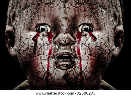 Close up Horror photo of a Cracked Scary Doll Crying Blood - stock photo