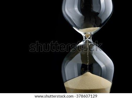 Close-up hourglass on black background - stock photo