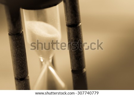 Close-up Hourglass on wood background , antique tone - stock photo