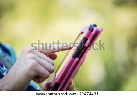 Close up Human Finger Pointing Tablet Screen in Pink Case. Captured Outdoor. - stock photo